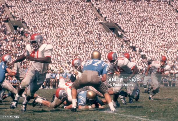 Dave Gibbs of the UCLA Bruins goes for the tackle as Robert Scott and Matthew Snell of the Ohio State Buckeyes block during an NCAA game on October 6...