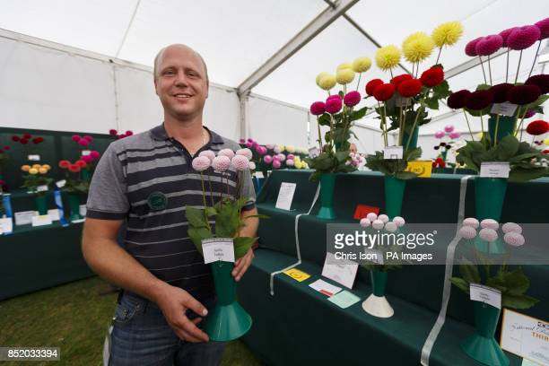 Dave Gillam proudly poses next to his Best Class In Show display of flowers at the National Dahlia Society's Annual Show at RHS Wisley in Surrey...