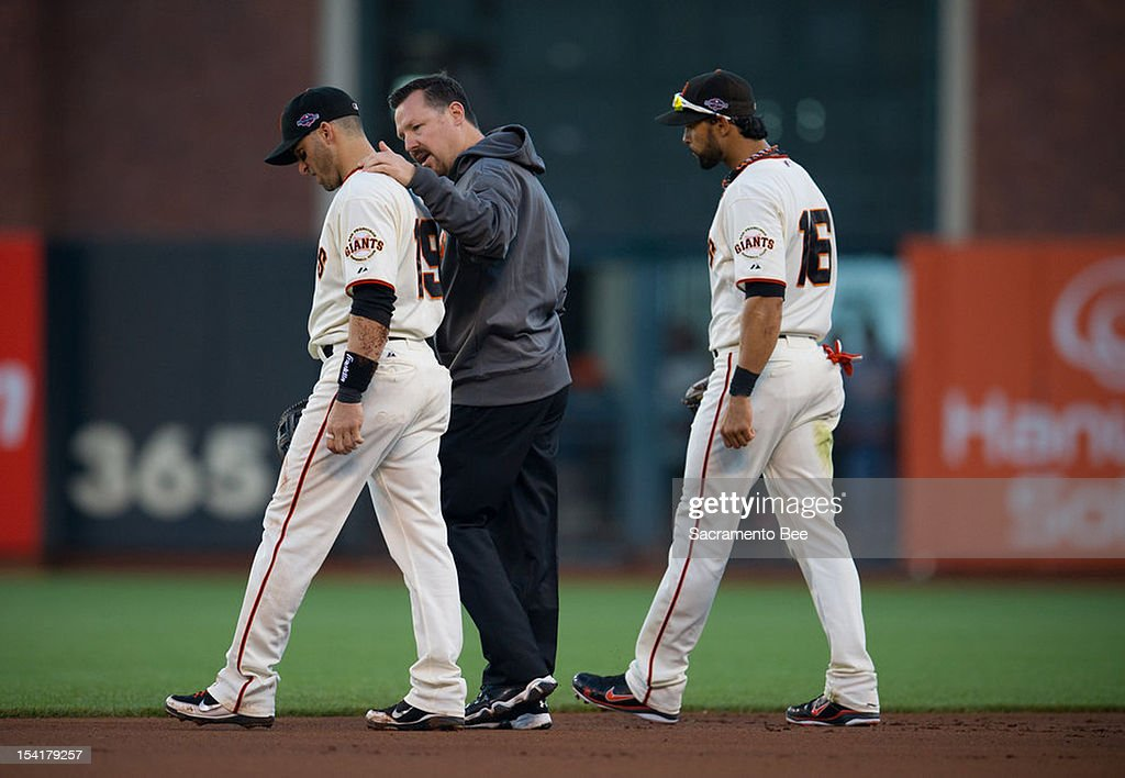 Dave Groeschner, Head Athletic Trainer for the San Francisco Giants talks with San Francisco Giants second baseman Marco Scutaro (19) after St. Louis Cardinals left fielder Matt Holliday (7) hit Scutaro breaking up a double play in the first inning during Game 2 of the National League Championship Series on Monday, October 15, 2012, at AT&T Park in San Francisco, California.