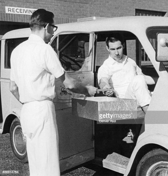 Dave Kolb left hands Dale Wenger a tray as Wenger prepares to leave on an errand for Spadling House in the special vehicle the convalescent home...