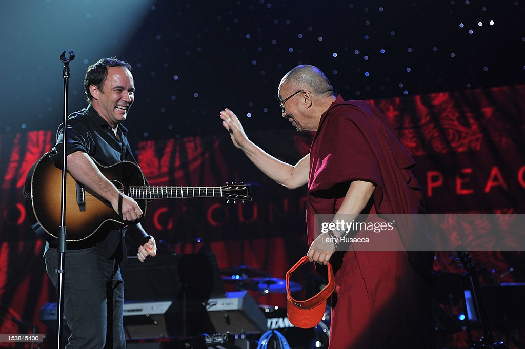 Dave Matthews and His Holiness the Dalai Lama shake hands onstage at the One World Concert at Syracuse University on October 9 2012 in Syracuse New...