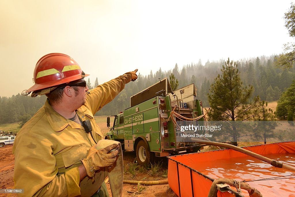 Dave McCrea, of Stanislaus National Forest SDF, points to the area where a 2,500 foot hose line from the orange tank at right, stretches to put out hot spots on fire division line Oscar to fight the Carstens Fire in the Sierra National Forest, June 17, 2013.