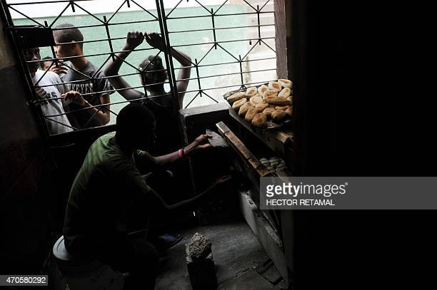 Dave places fresh dough into the oven at a small bakery in the neighborhood of Jalousie in the commune of Petion Ville PortauPrince on 21 April 2015...