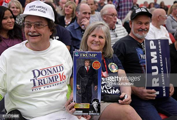 Dave Queen and Cindy McLaughlin hold a Trump speaking 'The Apprentice' doll during a rally with Republican presidential candidate Donald Trump at the...