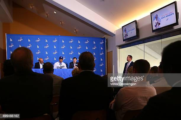 Dave Roberts center and Los Angeles Dodgers general manager Farhan Zaidi left look on as Dodgers President of Baseball Operations Andrew Friedman...