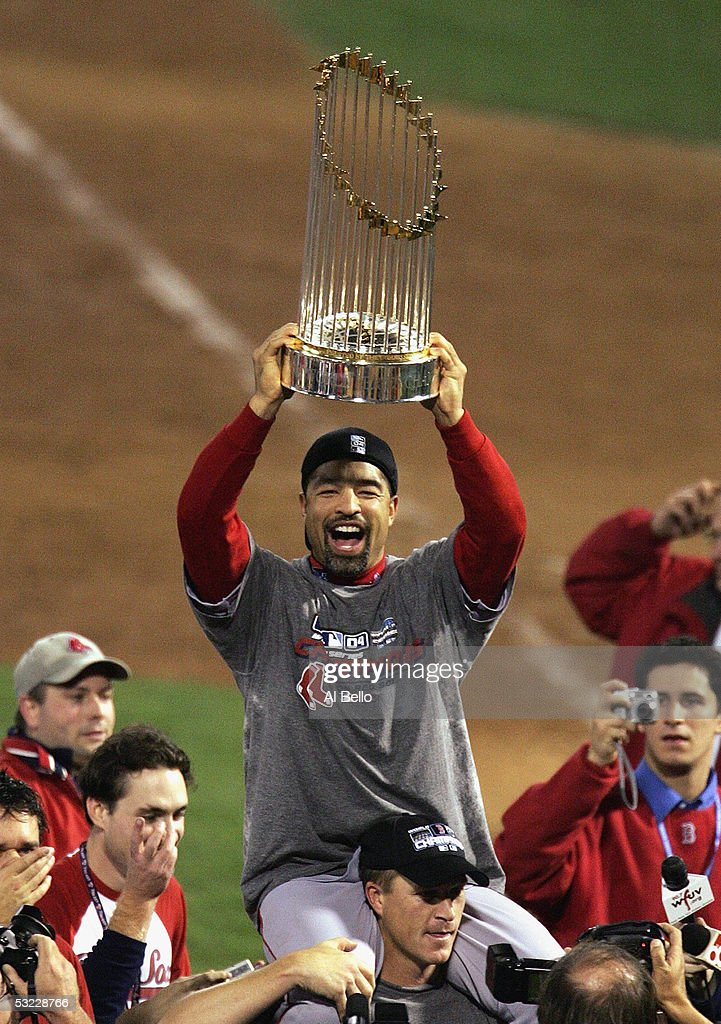 Dave Roberts #31 of the Boston Red Sox celebrates with the trophy over his head as he rides on the shoulders of teammate Mike Timlin #50 following the victory over the St. Louis Cardinals in game four of the World Series on October 27, 2004 at Busch Stadium in St. Louis, Missouri. The Red Sox defeated the Cardinals 3-0 to win the World Series 4-0.