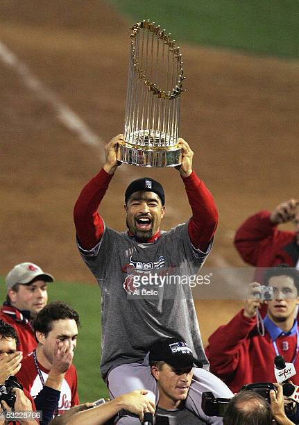 Dave Roberts of the Boston Red Sox celebrates with the trophy over his head as he rides on the shoulders of teammate Mike Timlin following the...