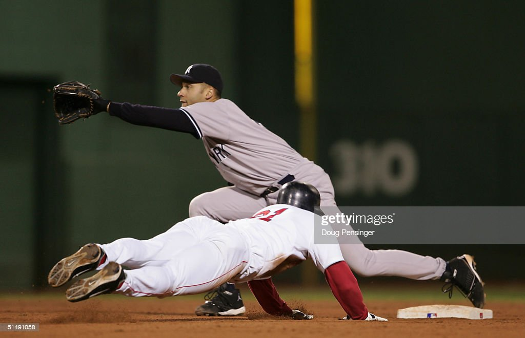 Dave Roberts of the Boston Red Sox steals second base while shortstop Derek Jeter of the New York Yankees waits for the throw in the ninth inning...