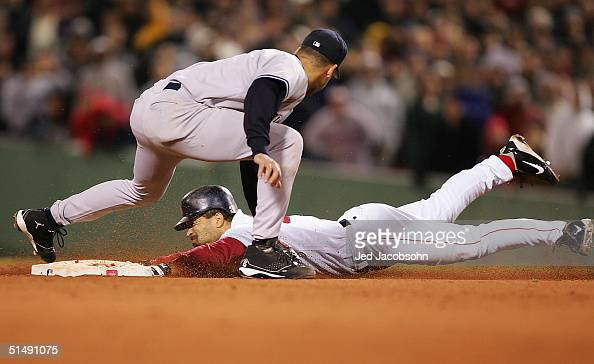Dave Roberts of the Boston Red Sox steals second base while shortstop Derek Jeter of the New York Yankees applies the tag in the ninth inning during...