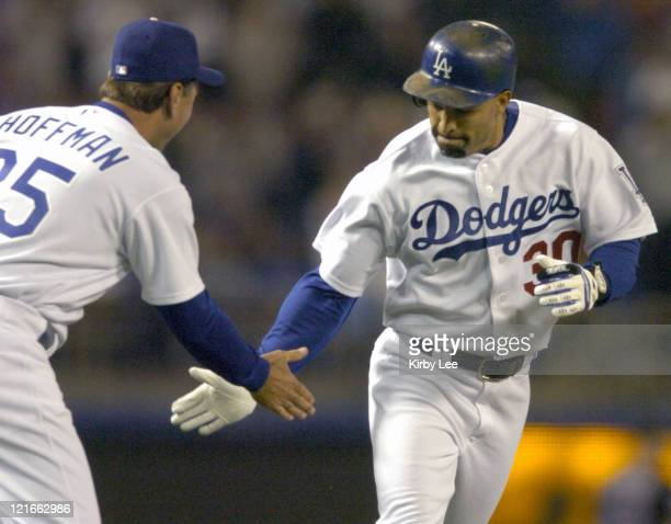 Dave Roberts of the Los Angeles Dodgers is congratulated by thirdbase coach Glenn Hoffman after a tworun home run in the third inning of a 32 victory...