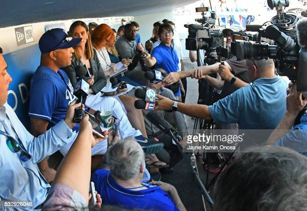 Dave Roberts of the Los Angeles Dodgers is interviewed by the media in the dugout before the game against the Chicago White Sox at Dodger Stadium on...