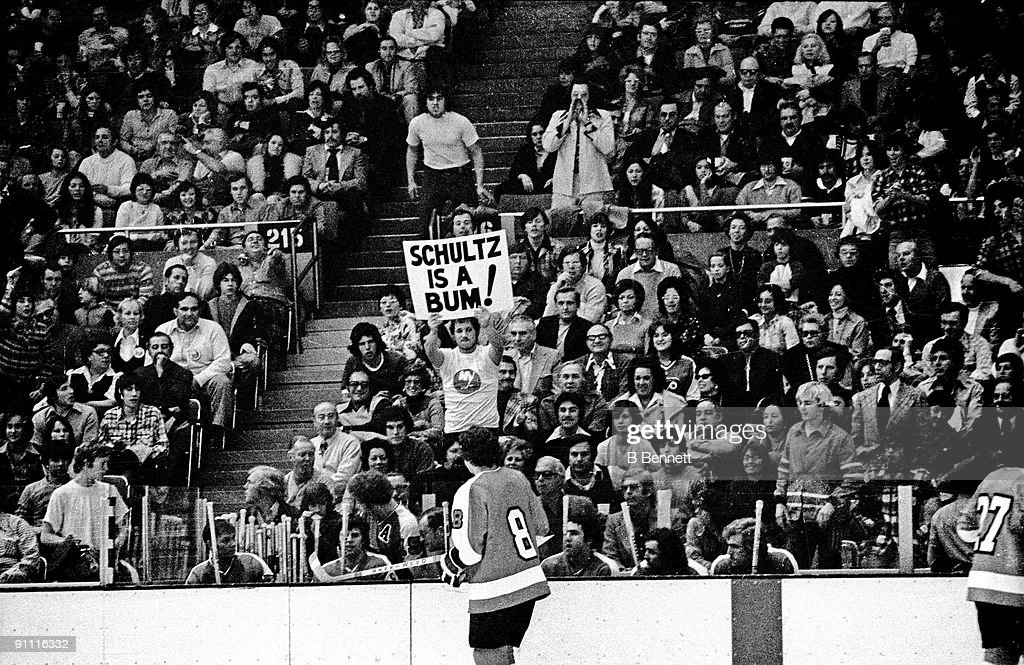 Dave Schultz of the Philadelphia Flyers skates in front of his bench as a fan of the New York Islanders holds a sign that reads 'Schultz is a bum'...
