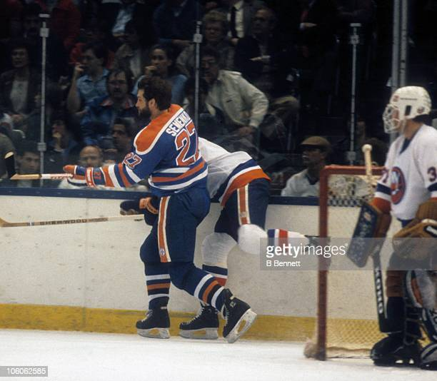 Dave Semenko of the Edmonton Oilers checks Ken Morrow of the New York Islanders during their game circa 1982 at the Nassau Coliseum in Uniondale New...
