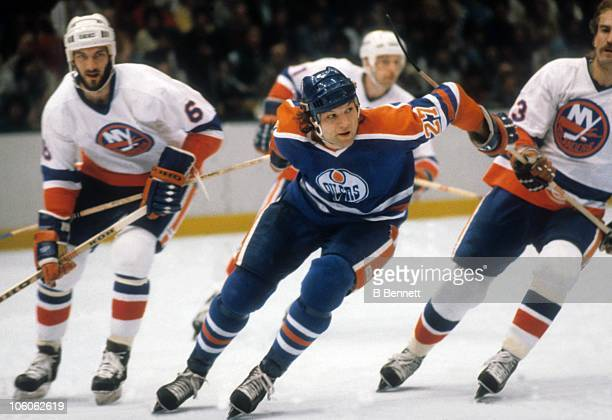 Dave Semenko of the Edmonton Oilers skates on the ice as Ken Morrow and Bob Nystrom of the New York Islanders follow during the QuarterFinals in...
