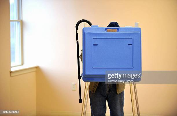Dave Silverman hangs his cane on the booth while voting in the State College Evangelical Free Church in State College Pennsylvania Tuesday November 5...