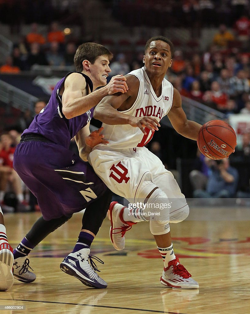 Dave Sobolewski of the Northwestern Wildcats grabs Yogi Ferrell of the Indiana Hoosiers during the second round of the 2015 Big Ten Men's Basketball...