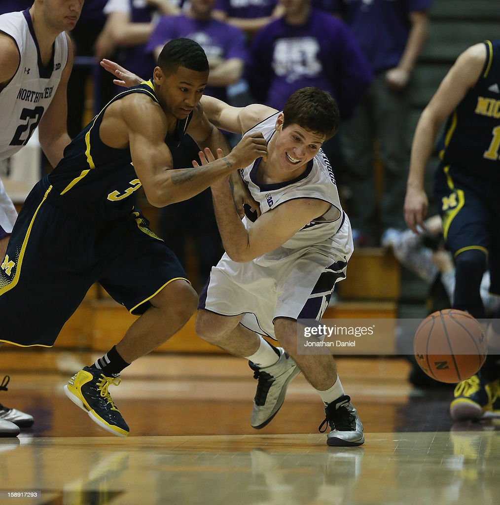 Dave Sobolewski #3 of the Northwestern Wildcats tries to hold off Trey Burke #3 of the Michigan Wolverines as they battle for a loose ball at Welsh-Ryan Arena on January 3, 2013 in Evanston, Illinois.