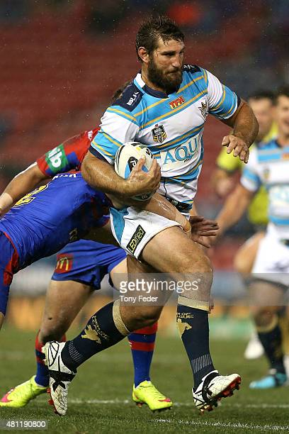 Dave Taylor of the Titans is tackled during the round 19 NRL match between the Newcastle Knights and the Gold Coast Titans at Hunter Stadium on July...
