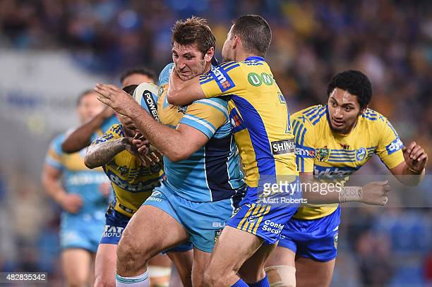 Dave Taylor of the Titans is tackled during the round 21 NRL match between the Gold Coast Titans and the Parramatta Eels at Cbus Super Stadium on...