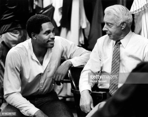 Dave Winfield of the New York Yankees talks with form Yankee Joe DiMaggio in the locker room before an MLB game circa 1985 at Yankee Stadium in the...