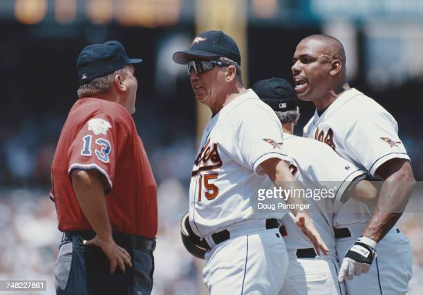Davey Johnson and team manager for the Baltimore Orioles holds back an angry Bobby Bonilla from umpire Derryl Cousins during the Major League...