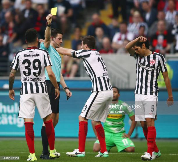 David Abraham of Frankfurt reacts as referee Harm Osmers shows the xyellow card to Omar Mascarell during the Bundesliga match between Eintracht...