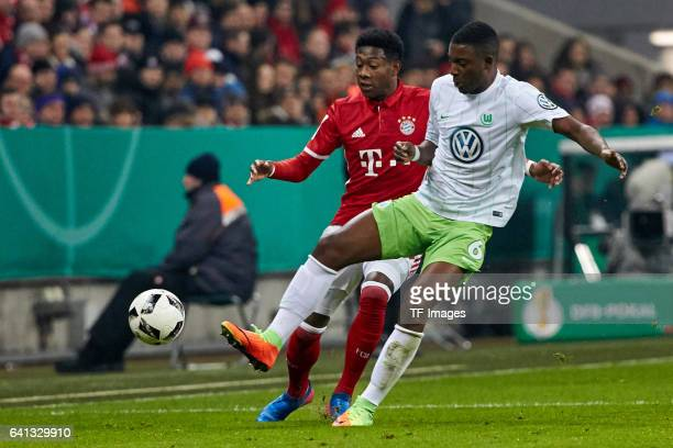 David Alaba of Bayern Muenchen andRiechedly Bazoer of VfL Wolfsburg battle for the ball during the DFB Cup RoandOf 16 match between Bayern Muenchen...