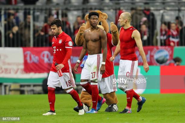 David Alaba of Bayern Muenchen Juan Bernat of Bayern Muenchen and Arjen Robben of Bayern Muenchen look on after the DFB Cup quarter final between...