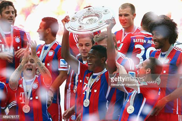 David Alaba of Bayern Muenchen lifts the Bundesliga championship trophy in celebration after the Bundesliga match between Bayern Muenchen and VfB...