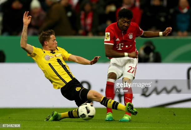 David Alaba of FC Bayern Muenchen and Erik Durm of Borussia Dortmund battle for the ball during the DFB Cup semi final match between FC Bayern...