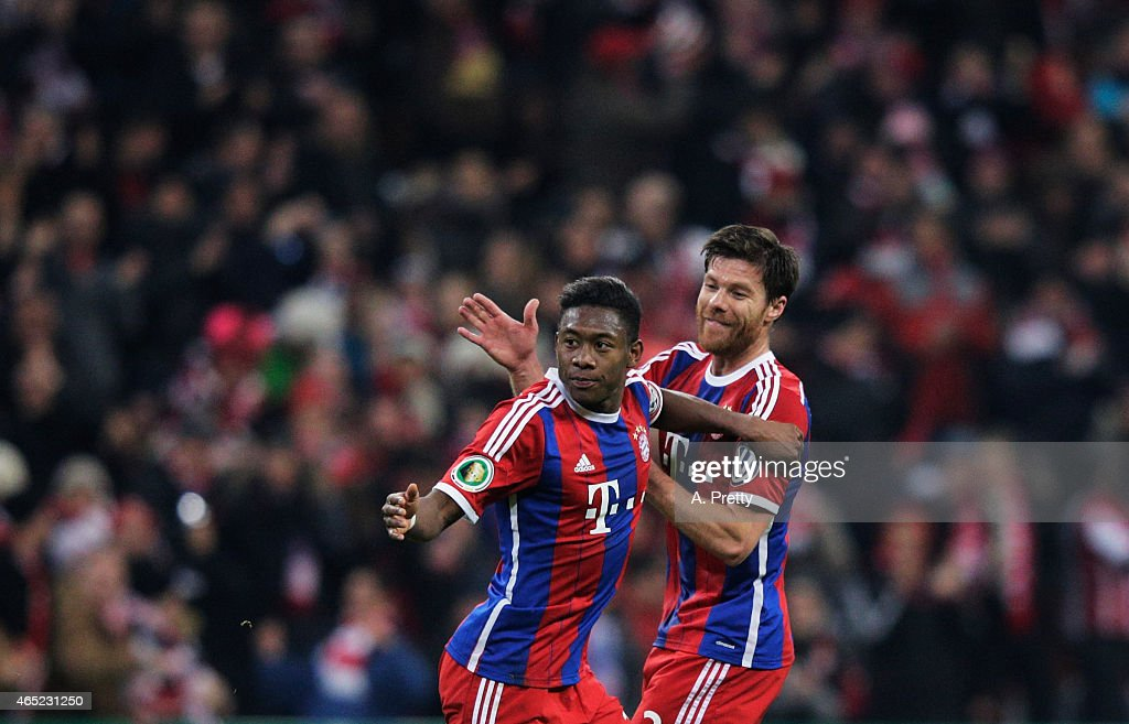 David Alaba of FC Bayern Muenchen celebrates with Xabi Alonso after scoring the first goal during the DFB Cup match between FC Bayern Muenchen and...
