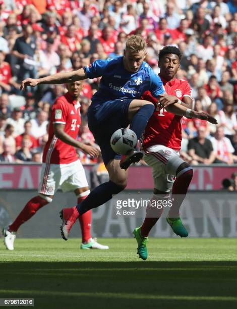 David Alaba of FC Bayern Muenchen fights for the ball with Felix Platte of SV Darmstadt during the Bundesliga match between Bayern Muenchen and SV...