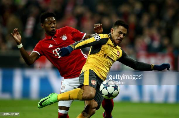 David Alaba of Muenchen and Alexis Sanchez of Arsenal battle for the ball during the UEFA Champions League Round of 16 first leg match between FC...