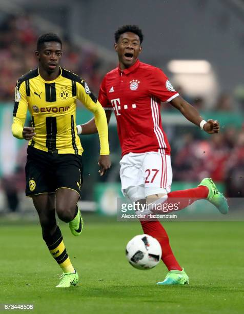 David Alaba of Muenchen and Ousmane Dembele of Dortmund battle for the ball during the DFB Cup semi final match between FC Bayern Muenchen and...