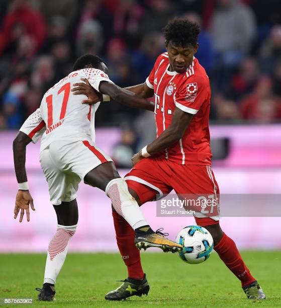 David Alaba of Muenchen is challenged by Bruma of Leipzig during the Bundesliga match between FC Bayern Muenchen and RB Leipzig at Allianz Arena on...