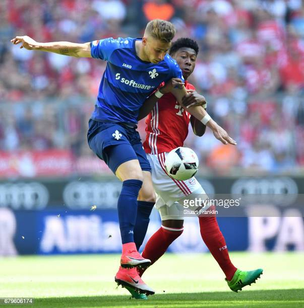 David Alaba of Muenchen is challenged by Felix Platte of Dramstadt during the Bundesliga match between Bayern Muenchen and SV Darmstadt 98 at Allianz...