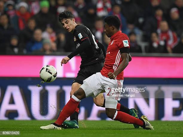 David Alaba of Muenchen is challenged by Kai Havertz of Leverkusen during the Bundesliga match between Bayern Muenchen and Bayer 04 Leverkusen at...