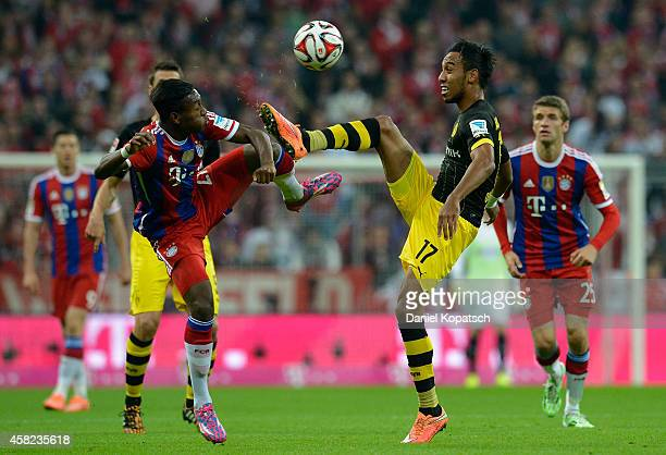 David Alaba of Muenchen is challenged by PierreEmerick Aubameyang of Dortmund during the Bundesliga match between FC Bayern Muenchen and Borussia...