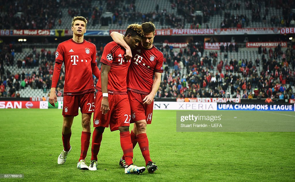David Alaba of Muenchen is comforted by Xabi Alonso after the UEFA Champions League Semi Final second leg match between FC Bayern Muenchen and Club Atletico de Madrid at the Allianz Arena on May 03, 2016 in Munich, Bavaria.