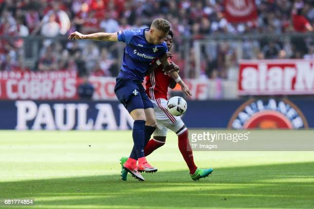 David Alaba of Munich and Felix Platte of Darmstadt battle for the ball during the Bundesliga match between Bayern Muenchen and SV Darmstadt 98 at...