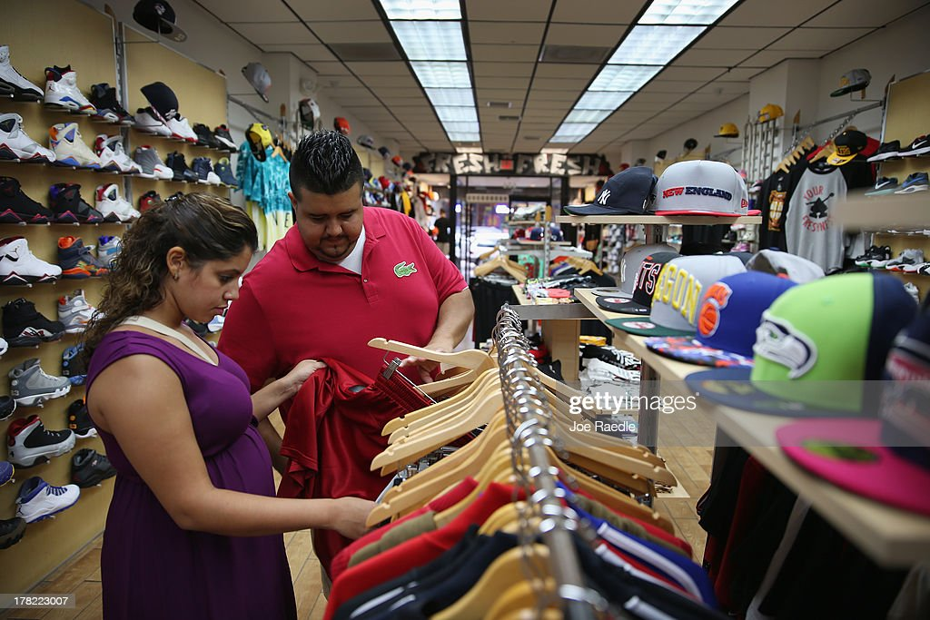 David Alvarez and Geral Abreu (L) shops at the C J Urban Wear store on August 27, 2013 in Miami, Florida. The Conference Board announced today that its index of consumer confidence rose to 81.5 this month from a revised 81.0 in July. Some economists reportedly had expected the latest index to edge slightly lower to 79.1.