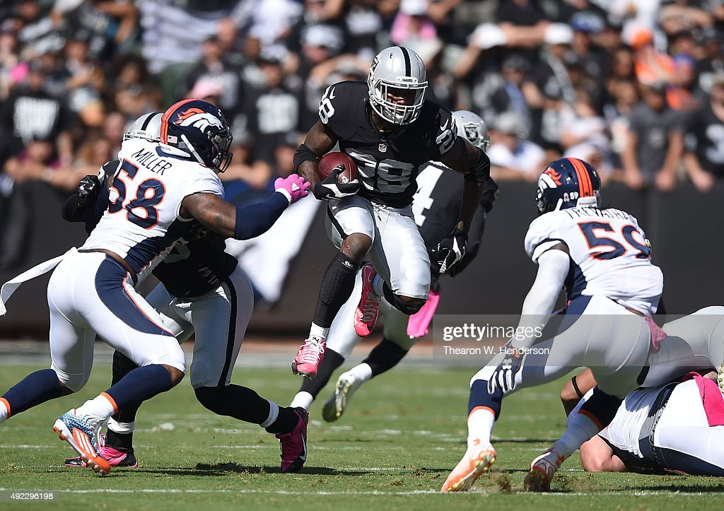 David Amerson of the Oakland Raiders jumps through the Denver Broncos defense in the first quarter at Oco Coliseum on October 11 2015 in Oakland...