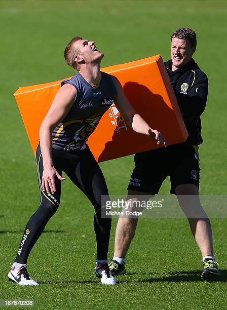 David Astbury contests for the ball against coach Damien Hardwick during a Richmond Tigers AFL training session at ME Bank Centre on May 2 2013 in...