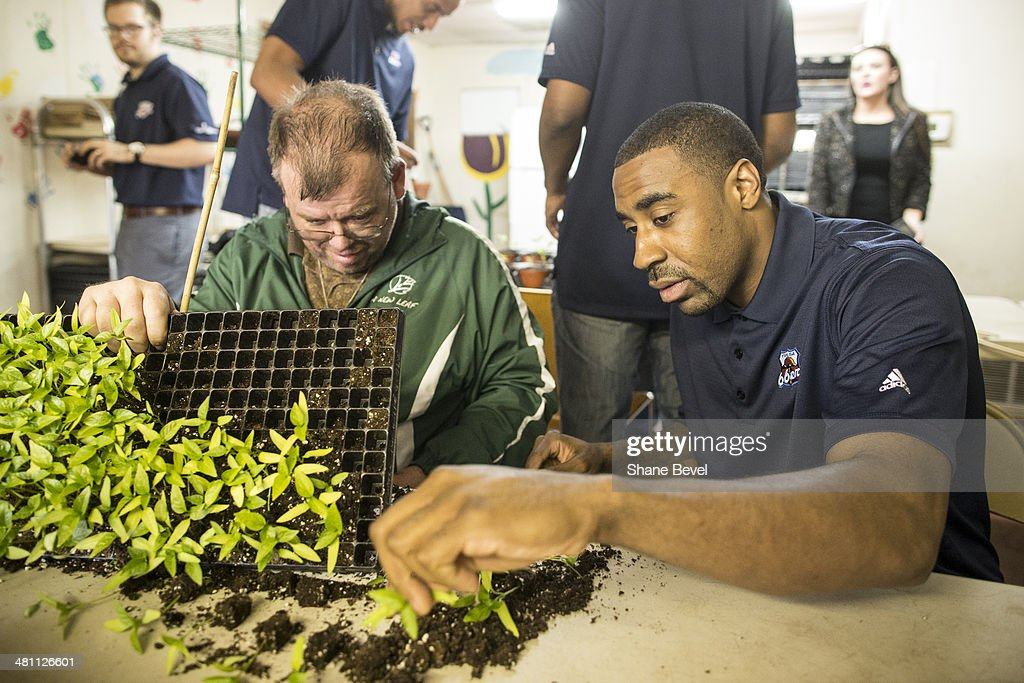 David Avey shows Reggie Williams of the Tulsa 66ers how to repot plants during the NBA D-League community relations event at A New Leaf, a non-profit that employs adults with developmental disabilities, on March 27, 2014 in Broken Arrow, Oklahoma.