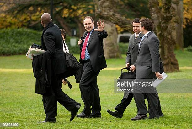 David Axelrod senior advisor to US President Barack Obama center waves while walking on the South Lawn of the White House to board Marine One with...