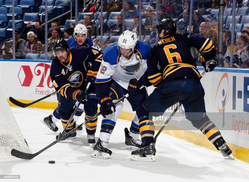 <a gi-track='captionPersonalityLinkClicked' href=/galleries/search?phrase=David+Backes&family=editorial&specificpeople=2538492 ng-click='$event.stopPropagation()'>David Backes</a> #42 and <a gi-track='captionPersonalityLinkClicked' href=/galleries/search?phrase=T.J.+Oshie&family=editorial&specificpeople=700383 ng-click='$event.stopPropagation()'>T.J. Oshie</a> #74 of the St. Louis Blues battle for the puck behind the net against <a gi-track='captionPersonalityLinkClicked' href=/galleries/search?phrase=Jamie+McBain&family=editorial&specificpeople=543199 ng-click='$event.stopPropagation()'>Jamie McBain</a> #4 and Mike Weber #6 of the Buffalo Sabres at First Niagara Center on November 19, 2013 in Buffalo, New York. St. Louis defeated Buffalo 4-1.