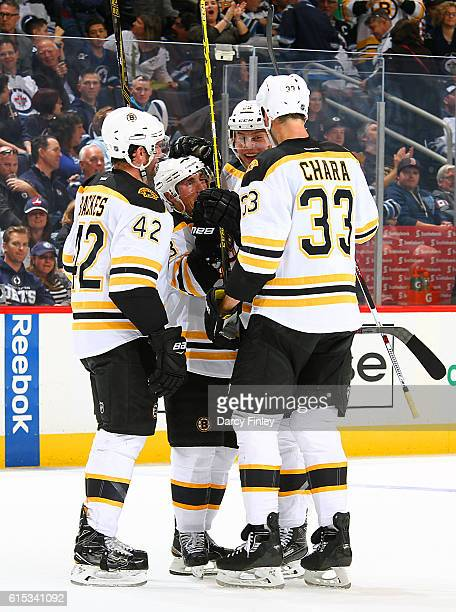 David Backes Brad Marchand Brandon Carlo and Zdeno Chara of the Boston Bruins celebrate a third period goal against the Winnipeg Jets at the MTS...