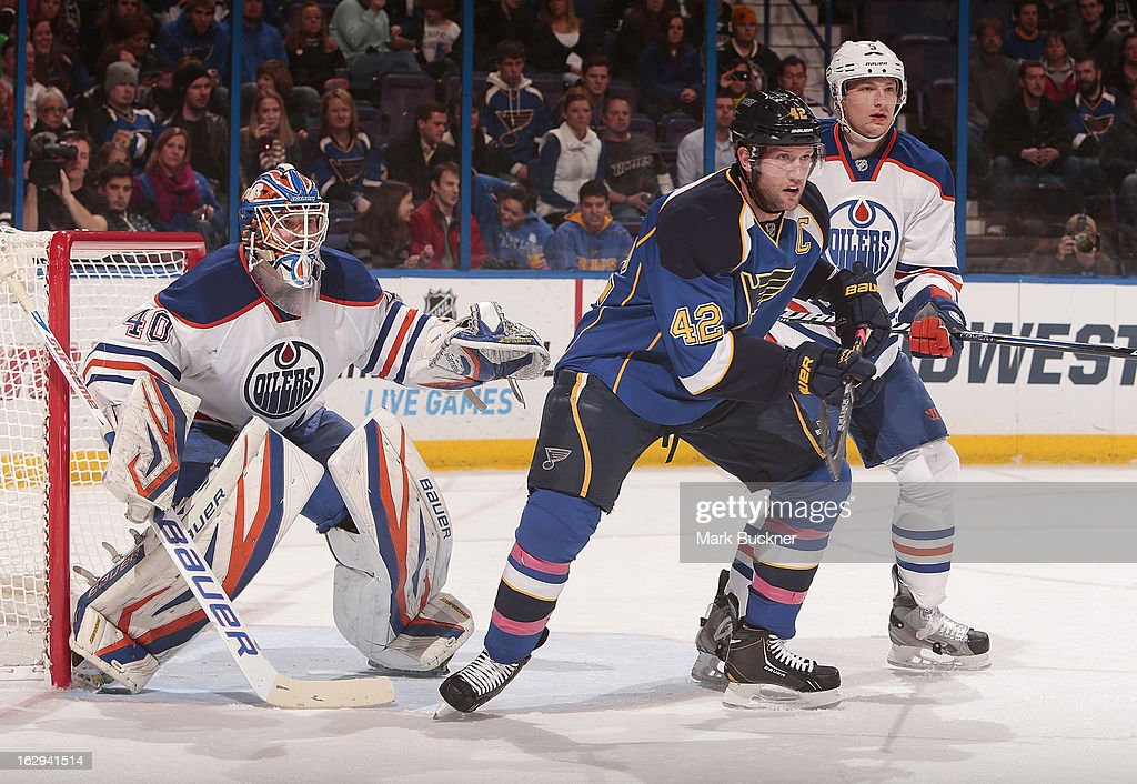 David Backes #42 \ob looks for a pass as Ladislav Smid #5 and goalie Devan Dubnyk #40 of the Edmonton Oilers defend in an NHL game on March 1, 2013 at Scottrade Center in St. Louis, Missouri.