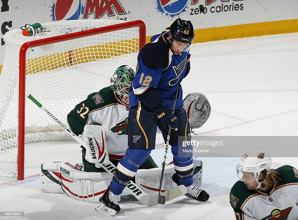 David Backes #42 of the St. Louis Blues deflects the puck in front of Niklas Backstrom #32 of the Minnesota Wild in an NHL game on January 27, 2013 at Scottrade Center in St. Louis, Missouri.