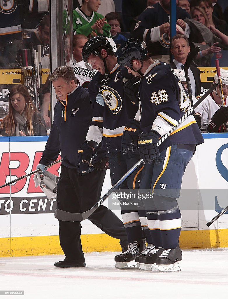 <a gi-track='captionPersonalityLinkClicked' href=/galleries/search?phrase=David+Backes&family=editorial&specificpeople=2538492 ng-click='$event.stopPropagation()'>David Backes</a> #42 of the St. Louis Blues is assisted off the ice by teammate <a gi-track='captionPersonalityLinkClicked' href=/galleries/search?phrase=Roman+Polak&family=editorial&specificpeople=2109482 ng-click='$event.stopPropagation()'>Roman Polak</a> #46 and a member of the training staff in an NHL game against the Chicago Blackhawks on February 28, 2013 at Scottrade Center in St. Louis, Missouri.